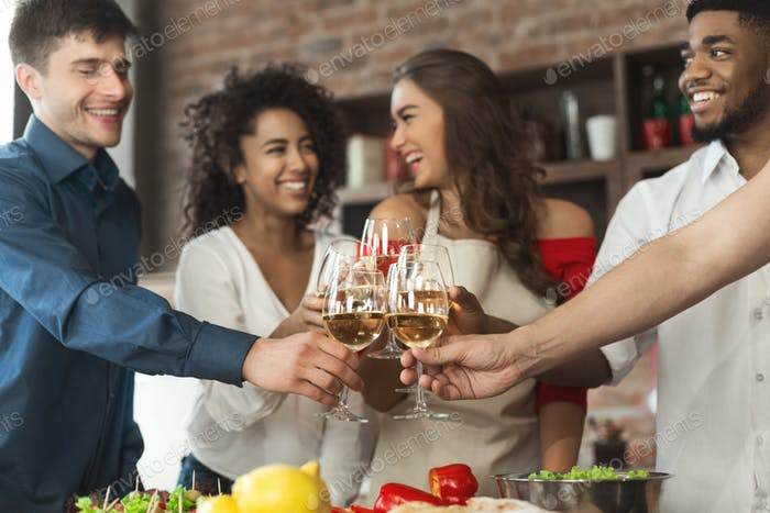 Happy multiracial friends clinking glasses while cooking