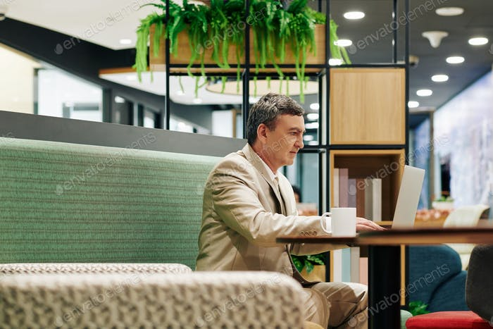 Middle-Aged Businessman In Cafe