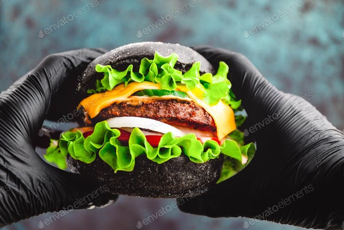 Hands in black gloves hold a big black burger with marble beef patty