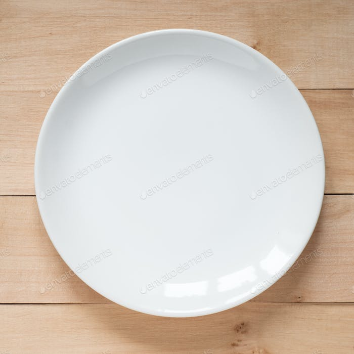 Empty White plate at wooden table