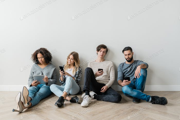 Intercultural milennials with smartphones sitting by white wall while texting