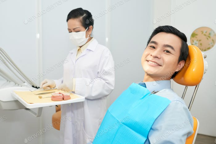 Smiling ethnic man in dental chair