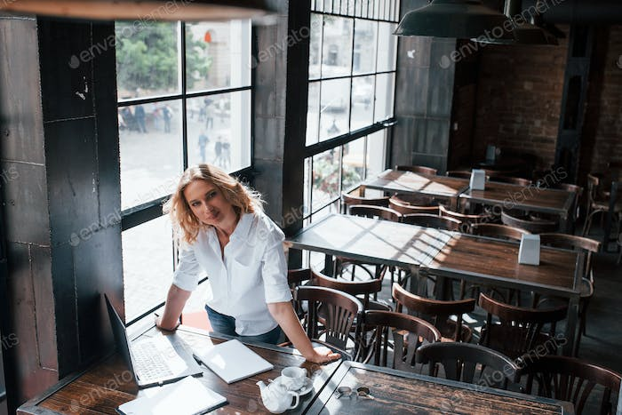 Partner is coming. Businesswoman with curly blonde hair indoors in cafe at daytime