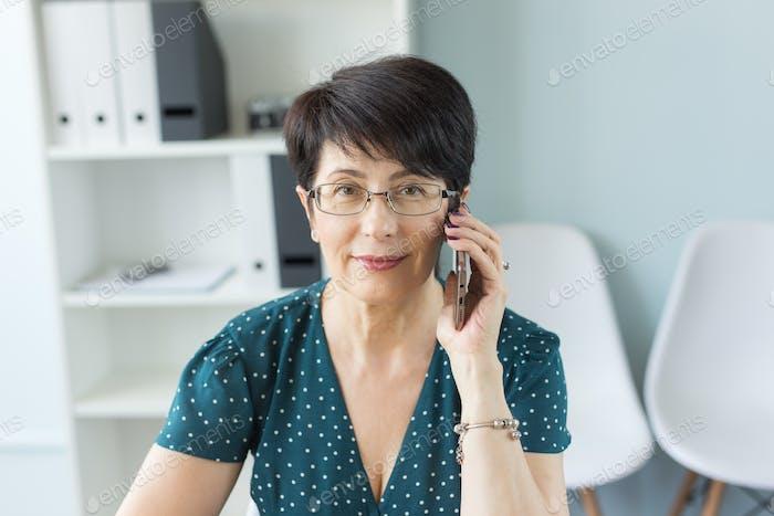 Menschen, Technologie und Kommunikationskonzept - Frau mittleren Alters anrufen auf Smartphone