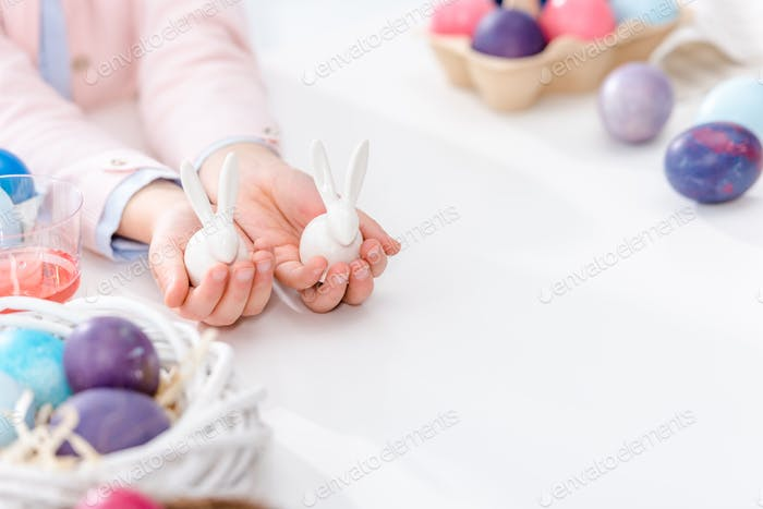 Close-up view of child showing bunny statuettes by Easter eggs