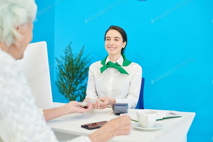 Cheerful manager getting money from customer for deposit