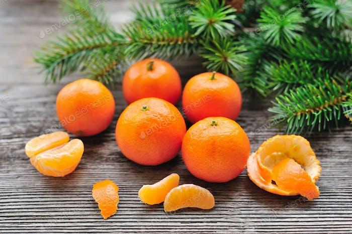 Mandarinen und Tannenzweige auf alten hölzernen Hintergrund