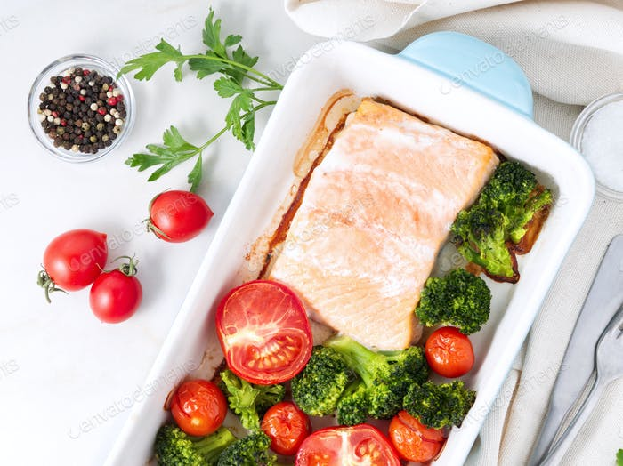 Fish salmon baked in oven with vegetables, broccoli. Healthy diet food, white marble backdrop