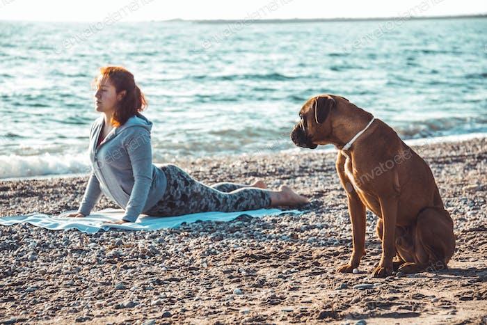 Mädchen tun Yoga und Stretching am Strand mit ihrem Hund