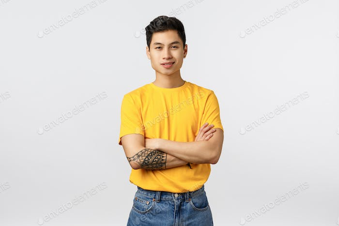 Handsome, confident and daring young asian man with tattooed arm, cross arms over chest, ready take