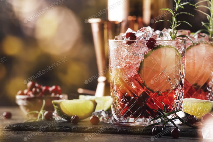Red alcohol cocktail with cranberries, ice and rosemary