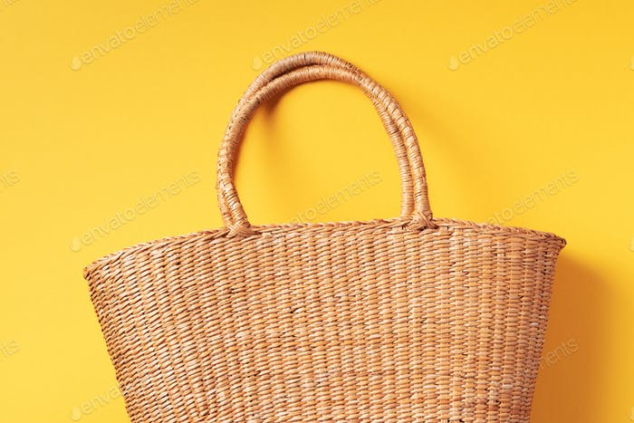 Women's straw bag on trendy yellow background. Top view. Copy space. Summer travel concept