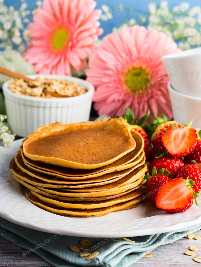 Stack of oatmeal pancakes with strawberries