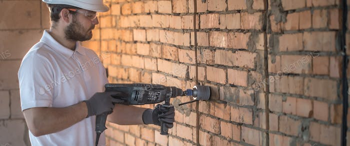 Handyman uses jackhammer, for installation, professional worker on the construction site.