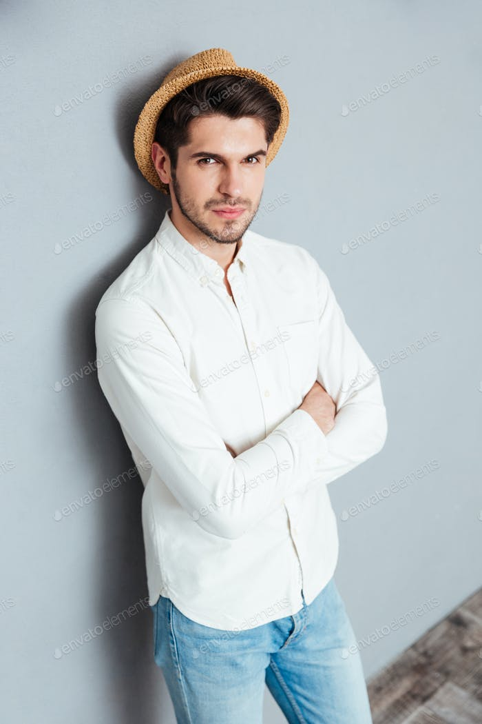 Portrait of a handsome young man standing with arms folded