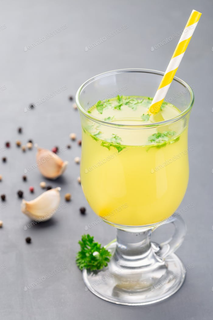 Chicken broth in glass garnished with chopped parsley, vertical