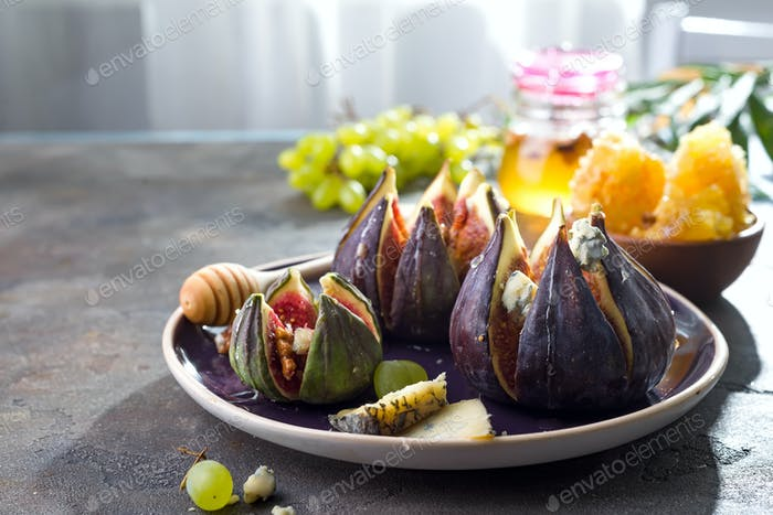 Gourmet appetizer of baked figs with goat cheese,walnuts and honey on ceramic plate