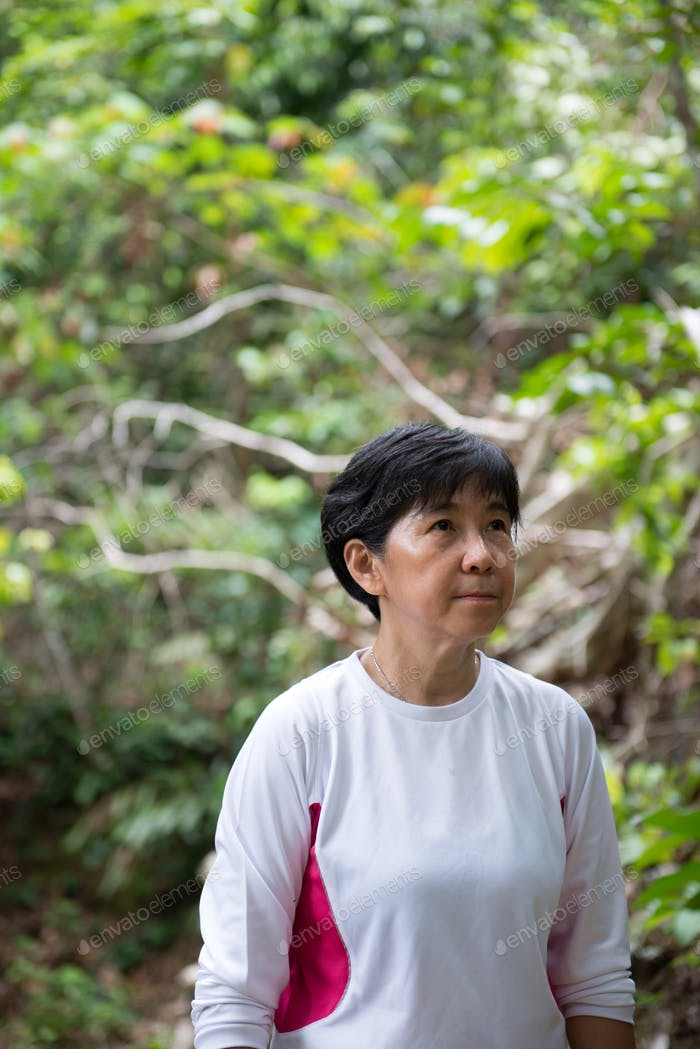 Asian woman hiking in jungle