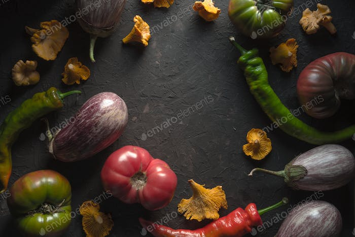 Frame of chanterelles, chili and vegetables on a gray table