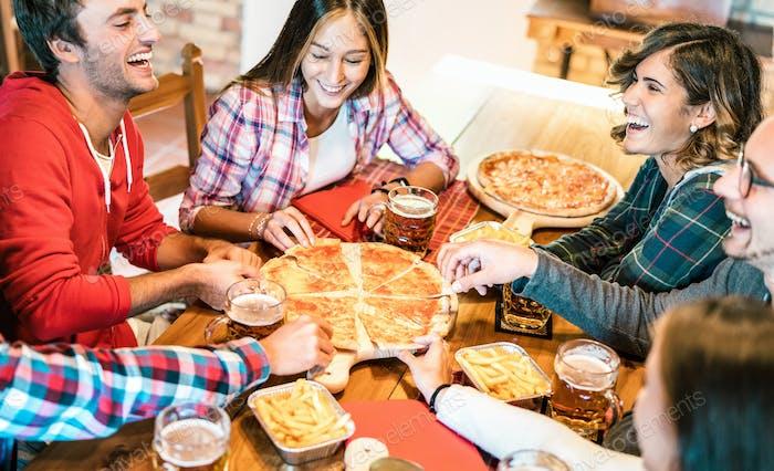 Jóvenes amigos en risa genuina mientras comen pizza en casa en la reunión familiar