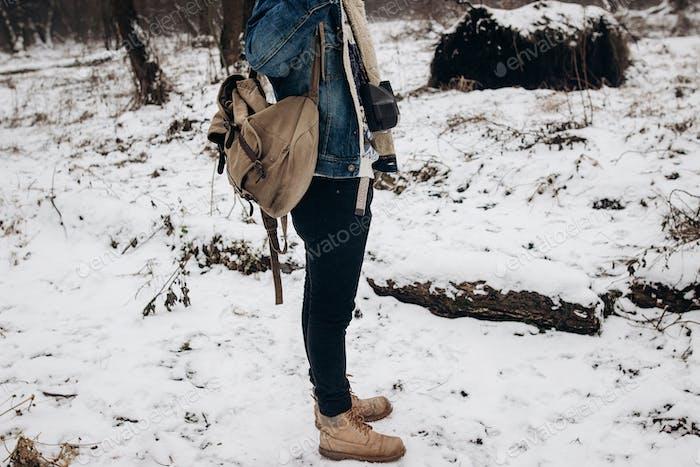 Hipster Reisender mit Rucksack zu Fuß in Nubuk-Schuhen im Winter verschneiten Wald