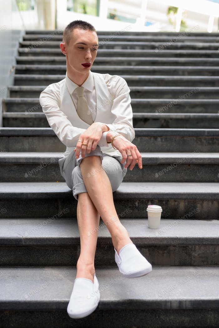 Young androgynous homosexual LGTB businessman sitting on stairs