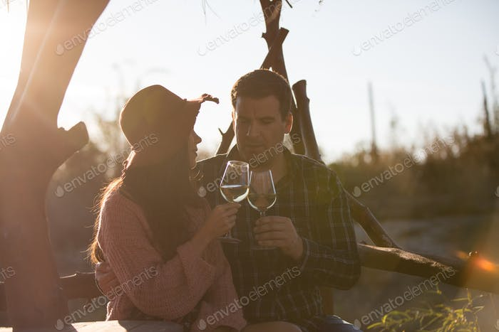 Cheerful young couple having a conversation sitting on a bench in a vineyard