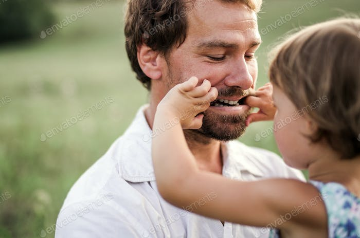 Young father in nature holding small daughter in the arms.