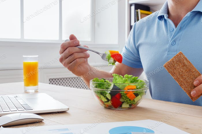 Unrecognizable man has healthy business lunch in modern office i