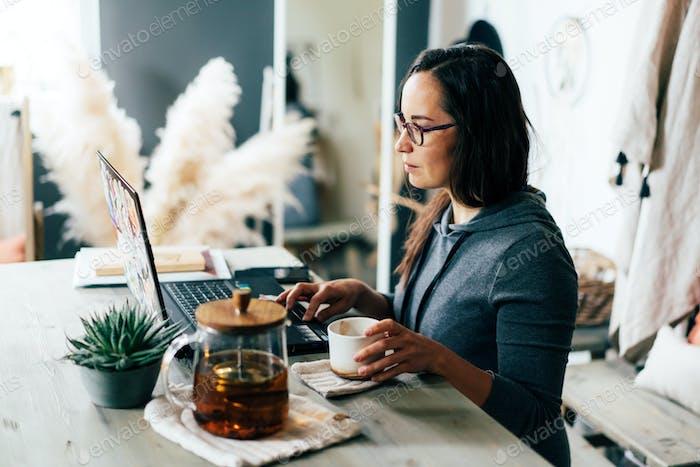 Eine Brünette in Gläsern funktioniert auf einem Laptop. Arbeiten Sie von zu Hause oder von einem gemütlichen Café aus.