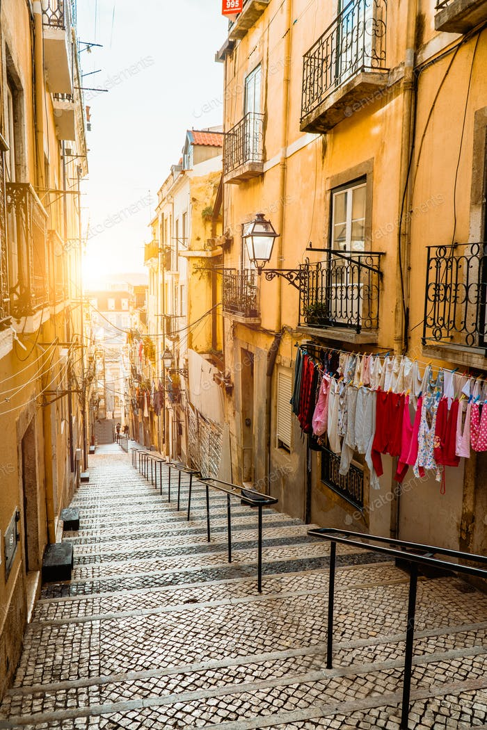 Staircase in the cobblestone street in Lisbon. Hanging laundry in typical narrow street. Sunset in