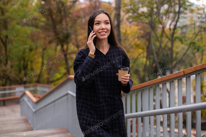 Young beautiful casual woman in coat with coffee to go happily talking on cellphone in park
