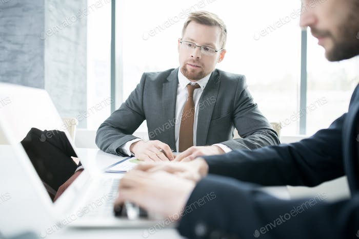 Two Business People Using Laptop