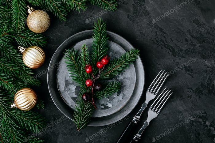 Christmas dinner background with empty plate and gold decor on dark table.