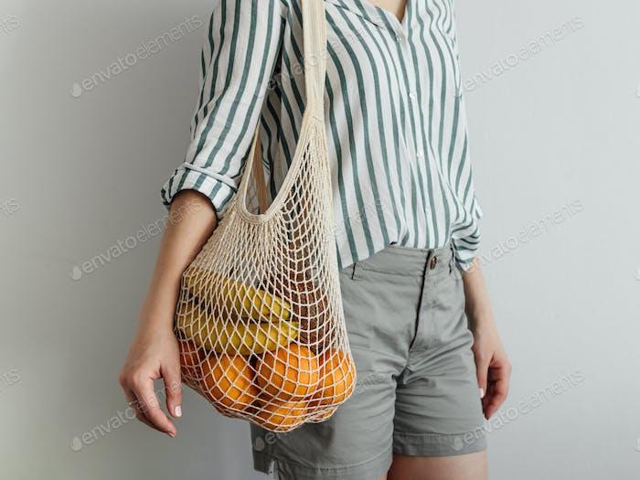 Frau stehend mit Mesh-Tasche auf der Schulter