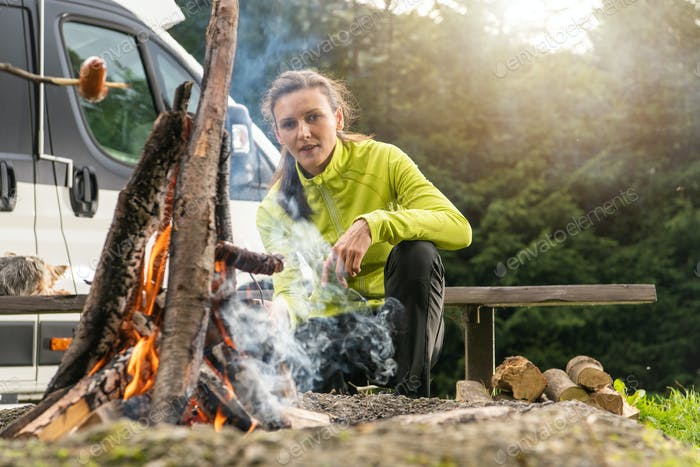 Young Woman Grilling Polish Sausage on Campfire Flames