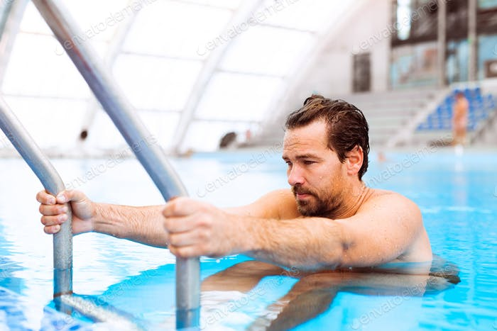 Man getting out of the indoor swimming pool.