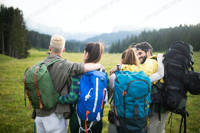 Four happy friends are looking on mountains and having fun together