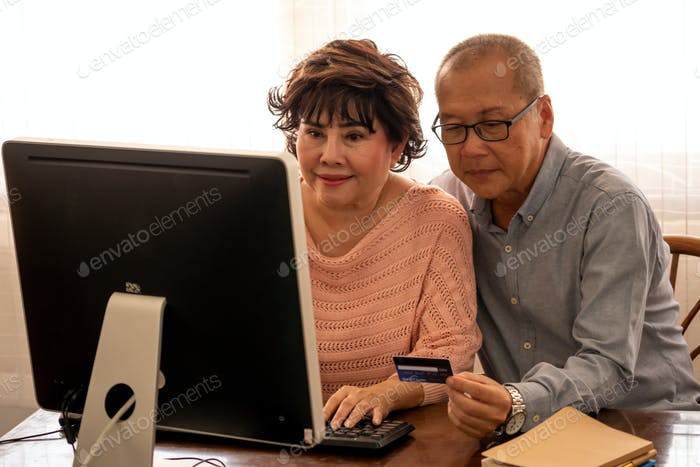 Asian couples doing financial transactions together by computer in the house.