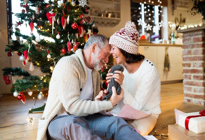 Senior couple in front of Christmas tree enjoying presents.