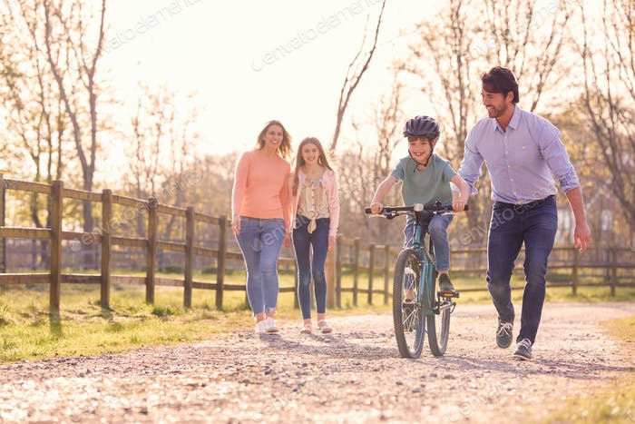 Family On Summer Walk In Countryside Teaching Son To Ride Bike