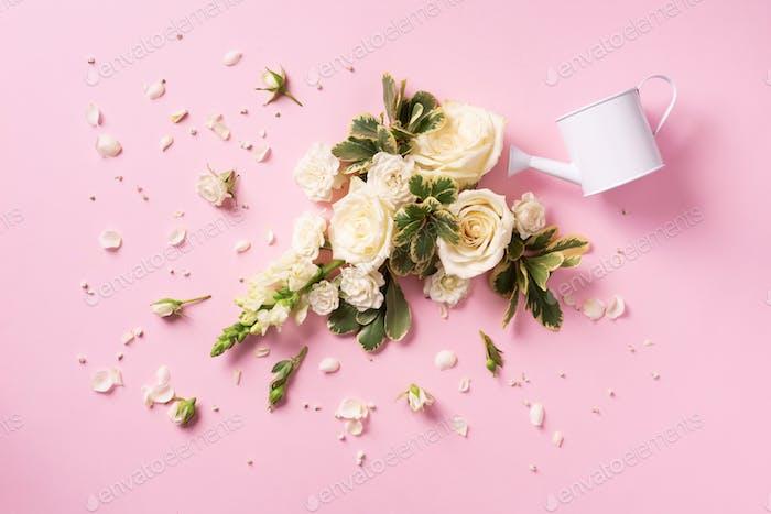 Gießkanne und weiße Rosenblüten, Blütenblätter über rosa Hintergrund. Ideen für kreatives Geschäft