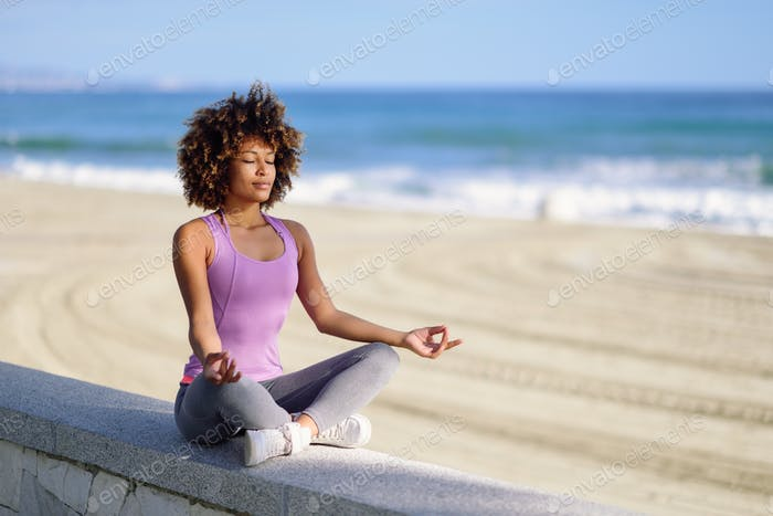 Black woman, afro hairstyle, in lotus pose with eyes closed in the beach