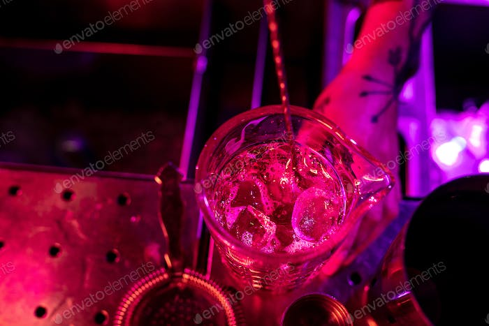 Close up of barman finishes preparation of alcoholic cocktail, shaking ice in multicolored neon