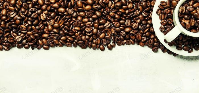 Geröstete Kaffeebohnen in einer weißen Tasse und Untertasse