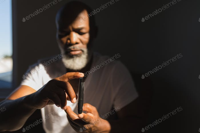 Front view of senior African American man with glucometer checking blood sugar level at home