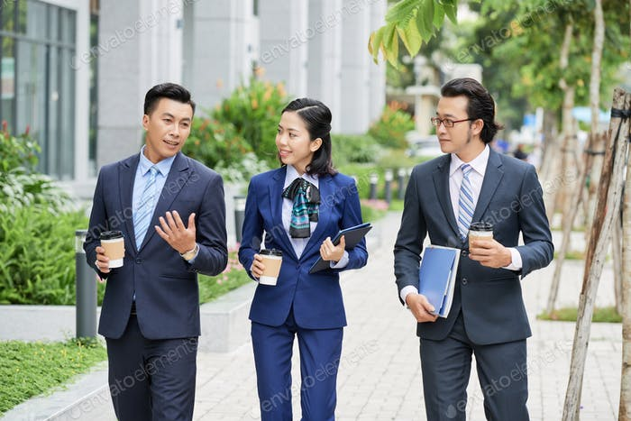 Modern businesspeople with coffee on street