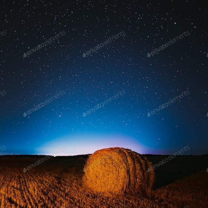 Cielo estrellado nocturno por encima de los pajares en el campo agrícola de verano. Estrellas nocturnas sobre paisaje rural