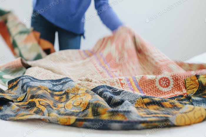 A woman spreading a fabric quilt over a bed in a bedroom.