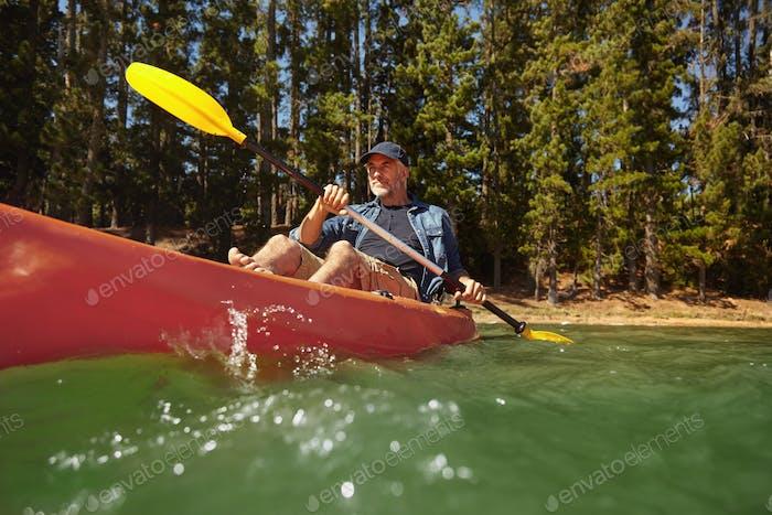 Reifer Mann paddeln ein Kajak in einem See